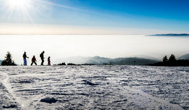 Family skiing silhouettes at a the piste Stock Photography