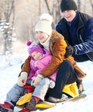Family sledding. In a winter park. Parents with child on sled Stock Photography