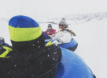 Family sledding down a hill on inflatable snow tubes in winter Royalty Free Stock Photo