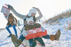 Family sledding in winter with enthusiasm. Holding christmas presents stock images