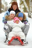 Family on sledge Stock Images
