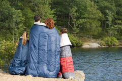 Family in sleeping bags by lake Stock Image