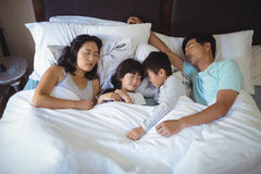 Family sleeping on bed in the bed room Royalty Free Stock Image