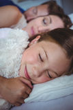 Family sleeping on bed Stock Images