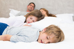 Family sleeping in bed. Siblings and parents sleeping in bed Royalty Free Stock Photography