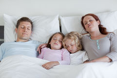 Family sleeping in the bed together Royalty Free Stock Images