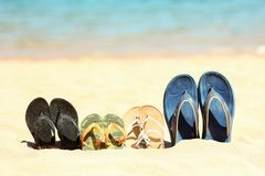 Family slippers on the sand on the beach. A Family slippers on the sand on the beach Stock Images