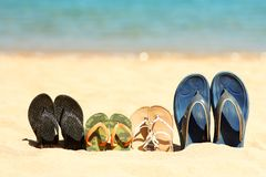 Family slippers on the sand on the beach. A Family slippers on the sand on the beach Stock Image
