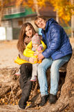 Family with small daughter sitting under tree Royalty Free Stock Photo