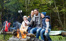 Family with smartphone taking selfie near campfire Royalty Free Stock Image