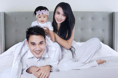 Family smiling at the camera on bed Royalty Free Stock Image