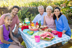 Family smiling at camera while having meal outdoors. Happy family smiling at camera while having meal outdoors royalty free stock photos