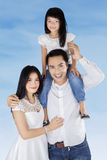 Family smiling at camera under blue sky Stock Photos