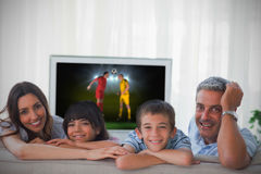 Family smiling at the camera with world cup showing on television Stock Photo