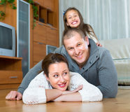 Family smiling at the floor Stock Photography