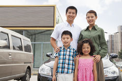 Family smiling in front of the car, portrait stock images