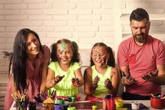 Family smiling with hands colored in paints. Girls drawing with mother and father. Children playing and learning with parents. Arts and crafts. Happy childhood royalty free stock photo