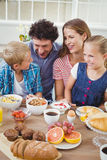 Family smiling while having breakfast at table. In house Royalty Free Stock Photography
