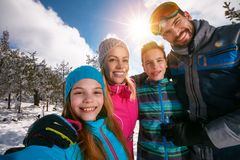 Family smiling and making selfie on winter ski vacation royalty free stock images
