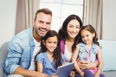 Family smiling while sitting on sofa at home Stock Photography