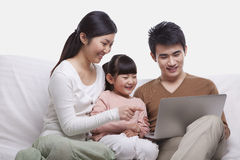 Family smiling and sitting together on the sofa looking at laptop, studio shot Royalty Free Stock Photo