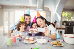 Family smiling while taking selfie during birthday celebration Stock Photography