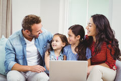 Family smiling and using laptop on sofa. Family smiling and using laptop while sitting on sofa at home Stock Image