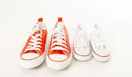 Family sneakers canvas shoes of father and child on white in single parent family concept. Conceptual image of gumshoes sneakers of father and baby son daughter stock photo