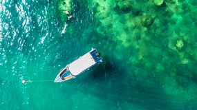 Family snorkeling near boat in clear tropical sea, aerial drone view from above, mother and kids snorkelers swimming in water. With corals on summer vacation in stock image