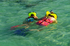 Family snorkling. Mother and daughter observing the bottom of the sea Royalty Free Stock Photo