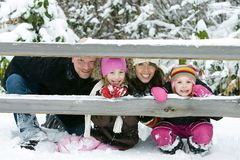 Family in the snow. A family of four looking through a fence in the snow Stock Photography