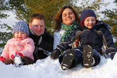 Family on a Snow Bank. A young Canadian family plays outdoors during winter Royalty Free Stock Photography