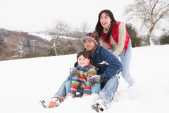 Family In Snow Riding On Sledge. Family In Snow Having Fun Riding On Sledge Royalty Free Stock Photography