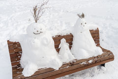 Family of snowman on a bench Royalty Free Stock Photo