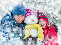 Family with a snowman Stock Photo