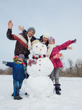 Family with a snowman. Happy beautiful family with two kids near snowman outside in winter time Royalty Free Stock Photography