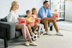 family with soccer ball sitting on sofa eating popcorn and looking away royalty free stock images