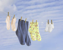 Family socks weighing on a  string. The family socks weighing on a  string fixed by clothespins Royalty Free Stock Photo