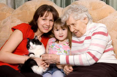 Family on a sofa with a cat royalty free stock photo