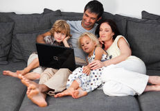 Family on a sofa with laptop Royalty Free Stock Images