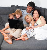 Family on a sofa with laptop Stock Image