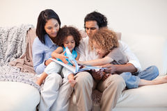 Family on the sofa looking at photo album together Royalty Free Stock Image
