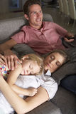 Family On Sofa Watching TV Stock Photo