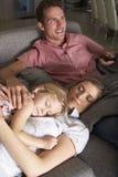Family On Sofa Watching TV Stock Photo