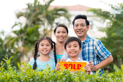 Family with sold sign. Happy Vietnamese family holding sold sign stock image