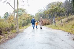 A family with a son go on road in the rain stock photos