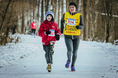 Family, a son and mother run together winter woods Stock Photo