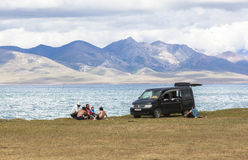 A FAMILY AT SONG KUL LAKE IN KYRGYZSTAN. This photo was taken on July, 2015 in Songkul lake, Kyrgyzstan. Song Kul is a high alpine lake in the Tian Shan stock photo