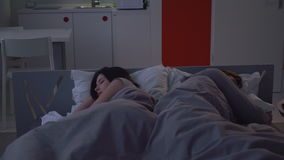 Family sound asleep. Family sleeping deeply in bed in small apartment at night. Woman and man lying on the white pillow covered with a blanket stock video