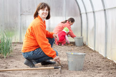 Family sows seeds  at greenhouse Royalty Free Stock Photography